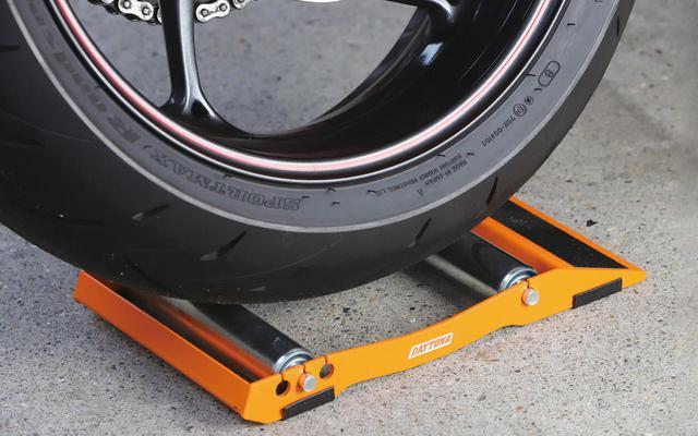 画像: スタンドのスロープ側から乗り上げるように車体を移動し、2本のローラー間にタイヤを位置させる。前輪に使う場合はハンドルを一杯に切った状態にしておくと作業しやすい。