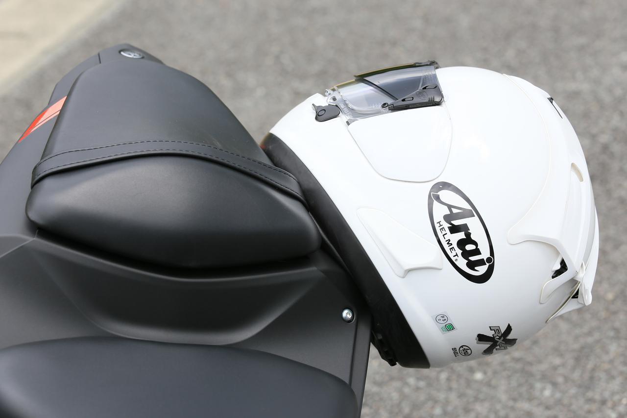 画像: ヘルメットホルダーはリアシートのフックを使うタイプ。両側に掛けることが可能。