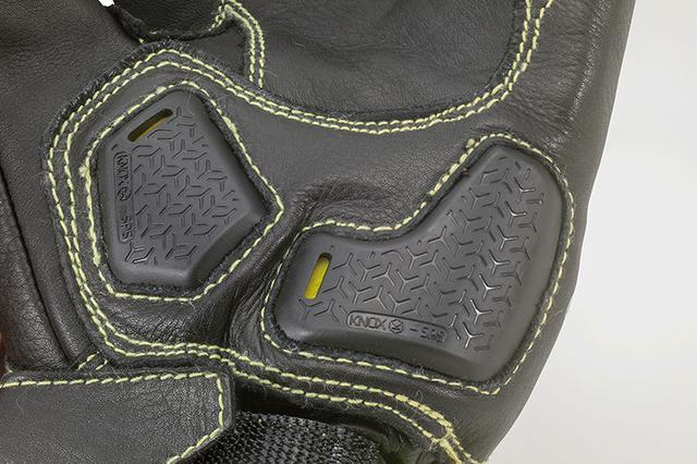 画像: カーボン製ナックルガードは甲部へのダメージ軽減に寄与するデザイン。薬指関節部にもレバーでの骨折を防ぐプロテクターを装備する。一方、掌部のKNOX製パームスライダーは滑走することで手首等の骨折を予防するものだ。同じく掌側は万一の転倒にもほつれ難い、ケプラー糸で縫製されているのだ。
