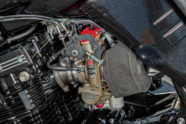 画像: スイングアームピボット上には、カタナでは効果があるとしてかつて多くの車両でも見られた左右フレーム連結・補強バー(写真のシルバーパーツ、左側が前方向)も入る。キャブレターはTMRφ40mmのMJN仕様で、排気系にはチタン4-1を組み合わせる。