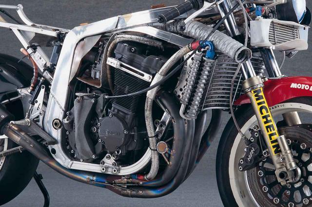 画像: 空油冷方式の特徴である短いフィンを持ったエンジンは、塗装部分の下地にサンドブラスト加工が施される。放熱効果を高めるため、少しでも表面積を増やすのが狙いだ。クラッチは、スズキ本社の設計となるRGV-Γと同方式の乾式。ヨシムラならではの、1-2/3-4気筒のエキパイをチャンバーで連結したデュプレックス方式、そして排気順序に従って集合するサイクロン方式を採用したEXシステムを装備。