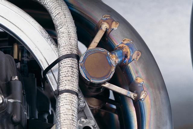 画像: エキパイの途中に適切な容量を持つチャンバーを設け、1-2/3-4気筒を連結するのがデュプレックス方式。高回転型エンジンでは不足しがちな低中速トルクを補う効果があり、当時のヨシムラは、ストリート用の排気管はもちろん、レーシングマシーンにも採用していた。