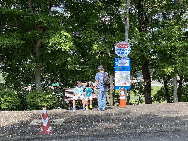 画像: バス停の横にはベンチがあり座りながら親子がバスを待っていました。