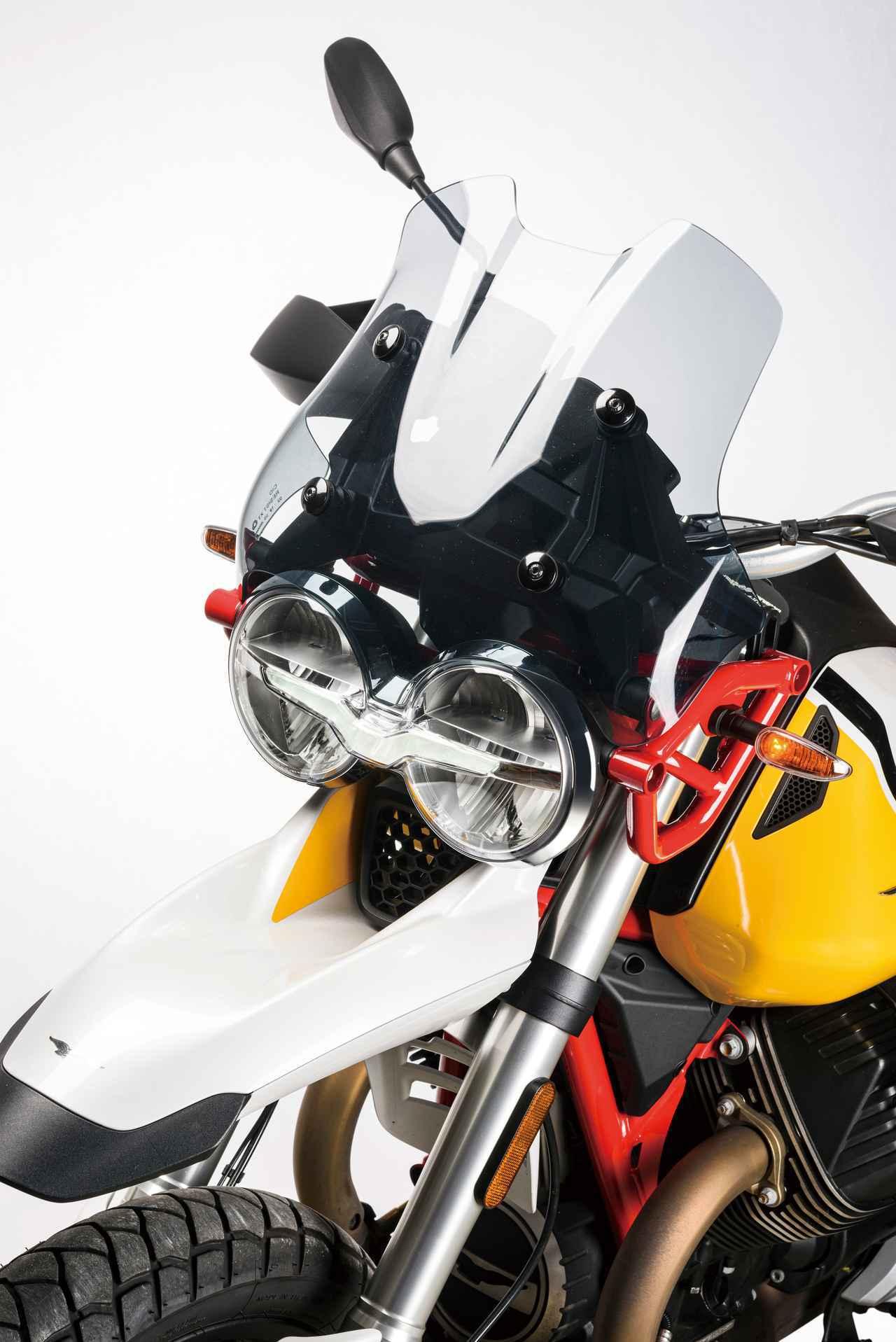 画像: ライダーを走行風による疲労から守る優れたウインドプロテクション性能を実現するために、風洞実験を繰り返して形状を決定したスモーク仕上げの大型ウインドスクリーン。往年のラリーマシンを想わせる大径の丸型ヘッドライトをデュアルで装備するが、中身は最新スペックのLEDヘッドライト。フロントフェンダーもパリダカ風味だ。