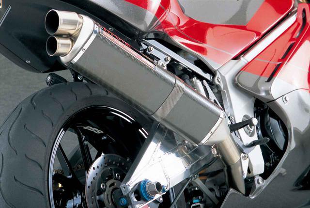 画像: サイレンサーは、当時のヨシムラの代名詞ともいえたトライオーバル。排気系の変更により987.8㏄(73╳59㎜)DOHC4バルブ4気筒は、クランクで160㎰/10800rpm、11.2㎏-m/8500rpmを公称するSTDに対し、12000rpmで170㎰を突破する最高出力と、10000rpmにて11㎏-mを超える最大トルクをエンジンダイナモで記録とヨシムラは発表。