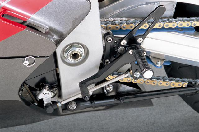 画像: アルミ削り出しの左右ステップも試作品で、ペダルと同軸のステップバーを受ける部分をフレームにボルト留めされる部分から分離、この時点で踏部の軸間距離を変えずに位置を可変させる機構が予定されていた。