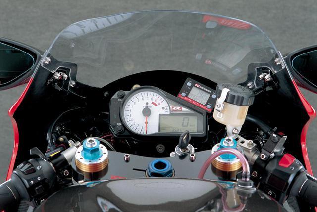 画像: 現状ではヘッドライトはカウルに装着されるが、アルミステーを製作して整備性を高めるとのことだ。12300rpmからがレッドゾーンの回転計と液晶ディスプレイの速度計によるメーターは純正品で、その右上にデジタルテンプメーターを装着。ハンドルやスイッチはSTDを流用、右スイッチの脇にあるのがEMSの3ウェイスイッチだ。