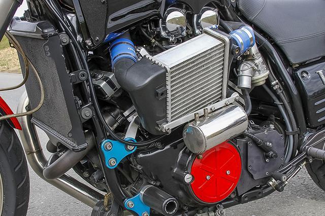 画像: この車両では4つの気筒からの排気はエンジン右のターボ(ユニット前側)を回し、後方から吸われた新気を圧縮=過給。圧縮で熱を持つため左側のインタークーラーで冷やしつつサージタンクに送り、そこから過給新気がキャブを通ってエンジンへ送られる仕組み。