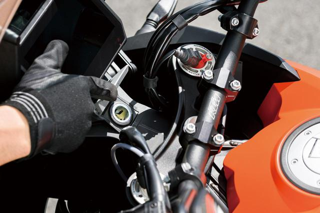 画像: メーターパネルの下には12V電源を供給するアクセサリーソケットが設けられている。さらにその右手には、USBポートも備えスマートフォンなどの収納に便利な蓋付きポケットもある。フロントフォークのトップから配線が伸びているのはセミアクティブサスの証。