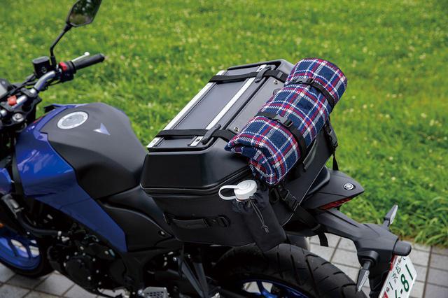 画像: テントやマットをバッグ上部に固定できるベルトも装備。フラップ上面が平らなので荷物が多い場合もツーリングネットで固定しやすい。