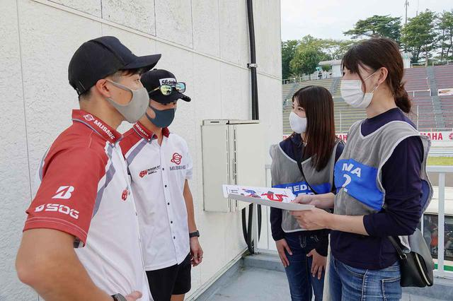 画像: 奥が名越選手。左手前の水野選手からのご連絡もお待ちしています! 実は、全日本ロードレースの開幕戦終了後、パドックでオートバイ女子部の大関さおりと梅本まどかがペーパークラフトのお願いをさせて頂きました。