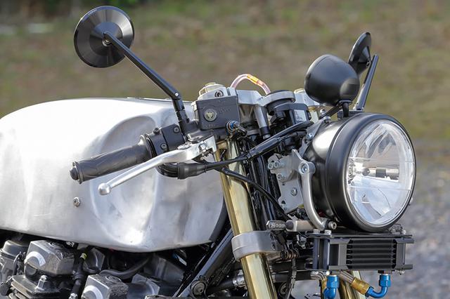 画像: 削り出しボディのミラーや超小型のLEDウインカーはドイツ・ハイサイダー製。ヘッドライトはステアリングヘッド部分から伸びた2枚のプレート型ステーでマウント、さらにヘッドライト下に伸びた丸パイプ下端にステーを作り、ウインカーをマウントしてある。