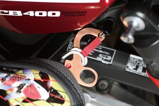 画像: あご紐のDリングに差し込んでヘルメットホルダーの金具に留める。Dリングと金具間の距離が増すことで使いやすくなる。