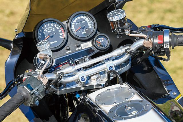 """画像: ハンドルはバータイプに換装し、ステムはケイファクトリー製。左右のマスターシリンダーはブレンボ・ラジアル。外装はビーター製アルミタンク+A-TECHカーボンで軽量化される。同店製コンプリートKATANA(シン・ハガネ)とGSX1100Sカタナ(ハガネ)の、刀身のようなシルバーに対してこちらは同様の色調をブラックで表現した""""クロガネ""""カラーに。塗装はいずれもアラタカデザインが行っている。"""