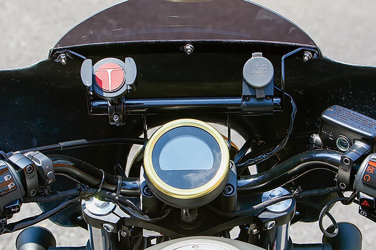 画像: フェアリング内側、メーターには被せるだけでカスタム感の高まるメーターリングを装着。写真はブラス(真鍮)製・みがき無。スチールクロームめっきもある。 メーター前方には今やツーリングの必携品となった各種ガジェットをマウントするキジマ・テックマウント 4G バーマウント ブラック+TECHグリッパー セットや、ガジェット類への電源となるキジマUSBポートキットも装着される。