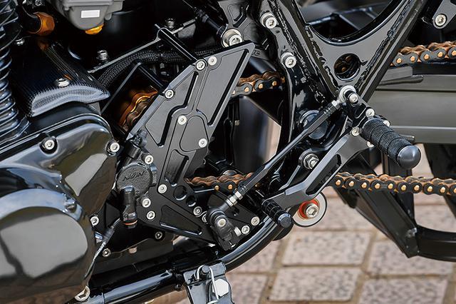 画像: フロントスプロケットカバー内側/ケース外側にはサンクチュアリーKOUGAによる「エヴォシステム」と「ロングアウトプットシャフト」を新たに追加して出力軸を精密両支持化、軸部の耐久性を高めてミッション振動を減らしている。リヤタイヤのワイド化→チェーンライン外側化の際に使うスプロケットもオフセットタイプでなくてOKになるメリットもある。ステップはタンデム側ともにナイトロレーシング。