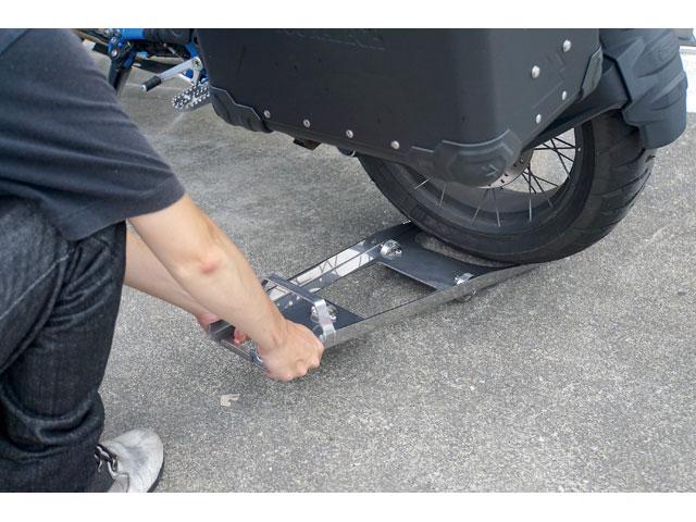 画像: 次に「バイクムーバープログレス」をリヤタイヤの下に差し込む。このとき先端のツノが確実にかかっていることを確認し、上から踏み込むとタイヤが浮く。そのままバイクの車体を押すと前輪を支点に弧を描くように動く。