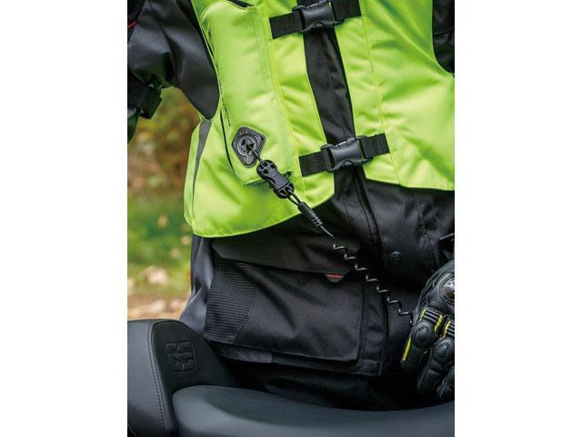 画像: 乗車時にバイクにつながっているワイヤーとエアバッグジャケットのコネクターを接続するだけで準備完了。ワイヤーは伸縮式なのでライディングのジャマになることはない。また降車時にコネクターを外し忘れても大丈夫。なぜなら作動するには約25〜35キロほどの張力が必要だから。ちょっと引っ張ったくらいではエアバッグが開いてしまうことはないのだ。