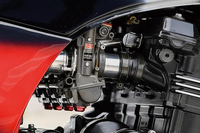 画像: キャブレターはTMRφ38mm-MJNのデュアルスタックファンネル仕様。フレームはワイドタイヤに対応するため、ドライブチェーンラインオフセット対応インライン処理が行われて、ナイトロレーシング・ダウンチューブ&ステップ コンビネーションキットⅢを追加する。車体剛性を上げつつもコンパクトに収まるのは現代のトレリスフレームにも通じる処理だ。