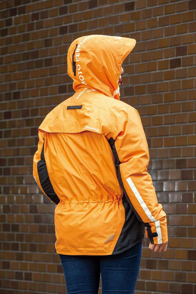 画像: フードは雨天時に役立つバイザー付き。背中上側にあるループに留められるので走行時のバタつきも防げる。