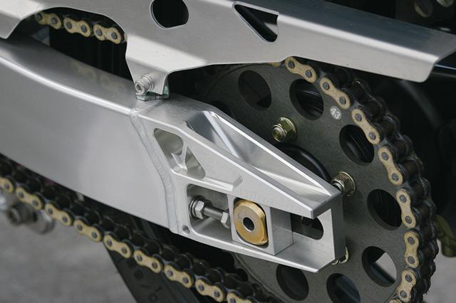 画像: 7N01材ハンドメイドのビッグ目の字スイングアーム。チェーン引きは、ウイリーで市販しているハイトコントロールBタイプ。アクスル位置を下にし、リヤ17インチ化によって起こる車高不足を補う製品だ。ホイールはマルケジーニ製マグ鍛造を履く。