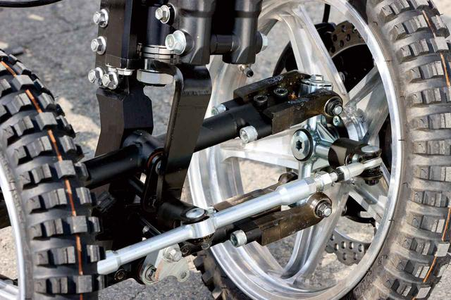 画像: ハンドルを左右へ切る力は前側のステム下の黒いプレートからシルバーのロッドに伝わり、左右ホイールのハブを動かしてステアリングを切る仕組み。