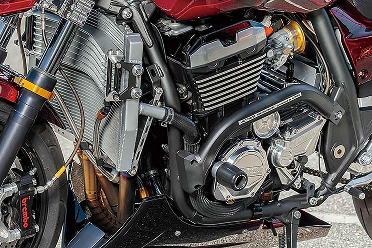 画像: エンジンは内部ノーマルで、ヤマモトレーシング・スロットルボディを装着してSEチューニングで調律済み。クラッチカバーやパルサーカバー、スプロケットカバーはウイリー製ビレット。冷却系はZRX系で定番の前後配置タイプで、ここにはナイトロレーシングラジエーター/オイルクーラーを装備。またエンジンサイドにはアクティブサブフレーム、下側にはアンダーカウルも装着して一体感を作り出す。