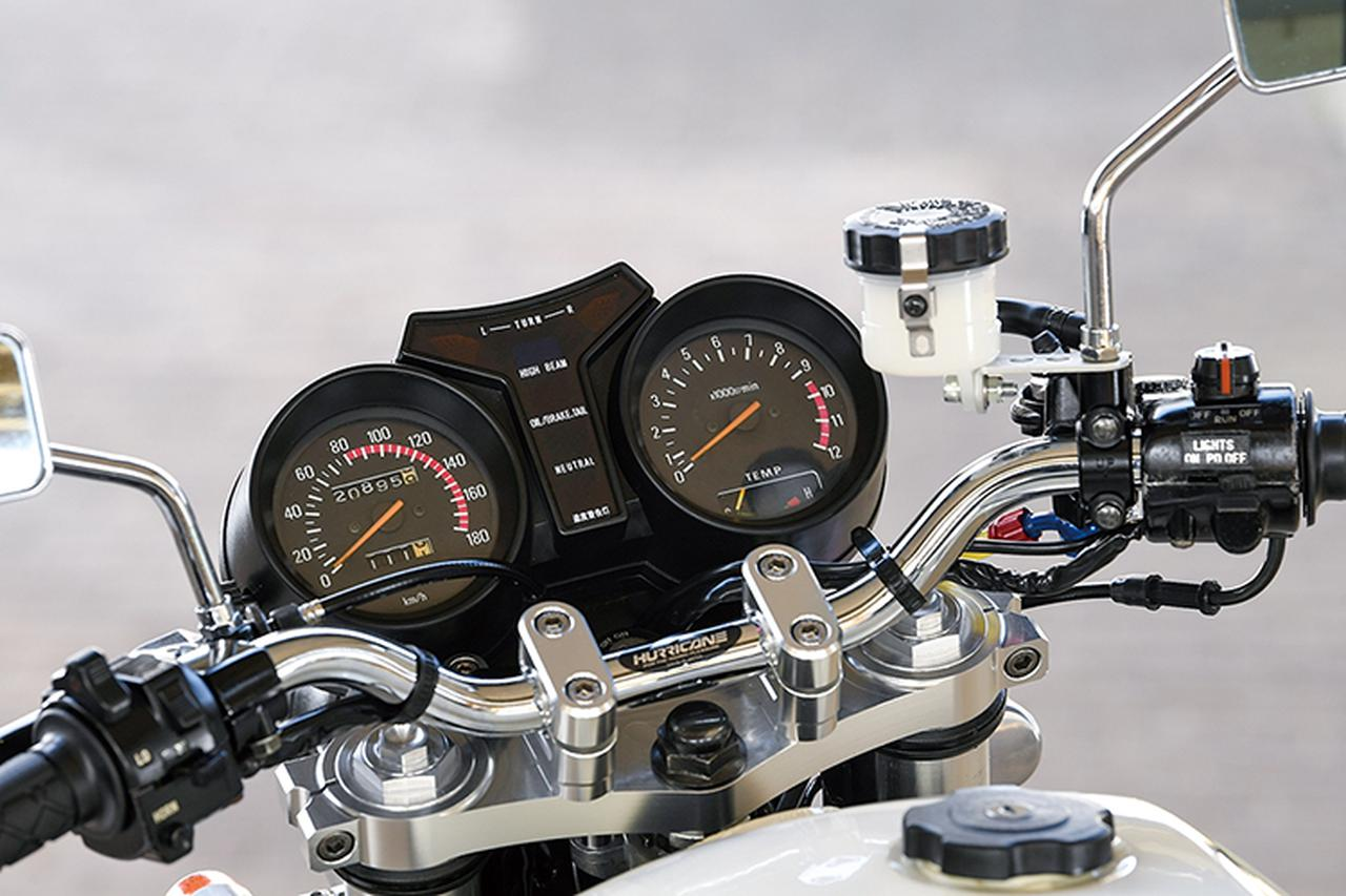 画像: 左の速度計、右のエンジン回転計の間にY字形状にインジケーターランプを配したメーターはRZ純正で、ステムはフロントフォークに合わせてTZR250R(V型エンジンの3XV)の純正パーツを使う。アッパーブラケットはHOT&COOL削り出し品を使い、ハリケーン・ハンドルバーをクランプしてある。
