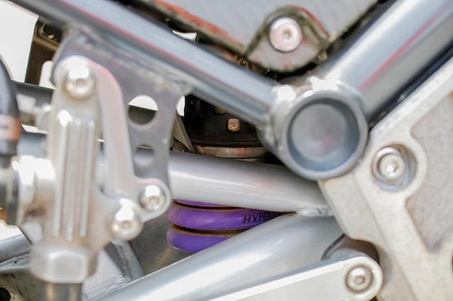 画像: 車体奥に見えるパープルのリヤスプリングはハイパープロ。リヤサスのリンクプレートも変更して車高をアップしている。リヤショック自体はペンタグラムで加工し、前後ともダンパーが効く特性に。