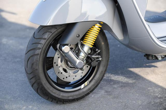 画像: リンクアーム式フロントサスペンションのスプリングもイエローになっている。前後ホイールは12インチ径で、タイヤのサイズはフロントが120/70、リアは130/70。φ220㎜のステンレス製ローターを採用するディスクブレーキにはABSも組み合わせられている。