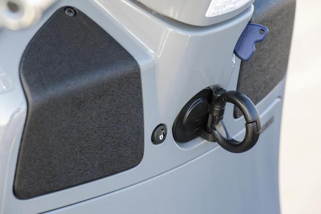 画像: ハンドルの真下には街乗り用途では重宝する折り畳み式のコンビニフックがあり、その左側にはシートオープンボタンが設けられている。