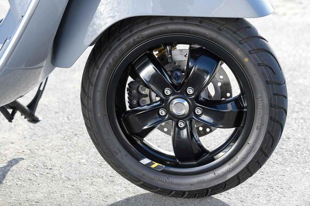 画像: フロントホイールが片持ち支持なのはベスパの伝統。かつてタイヤの品質が低かった時代に、パンク修理を想定してホイールの脱着を容易にしたことの名残りだという。ブラック仕上げの5本スポークホイールのリムにもイエローのワンポイントが。