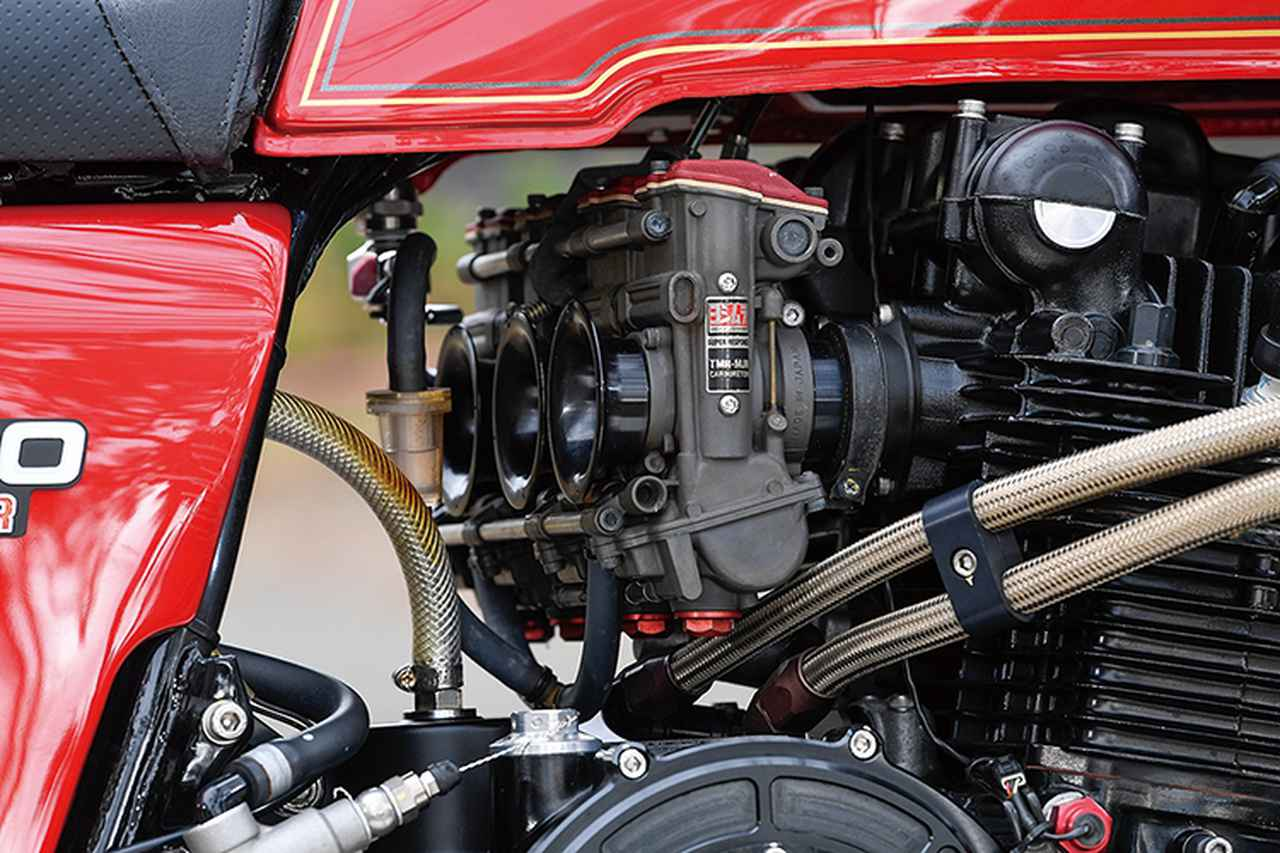 画像: ガンメタ×レッドのキャブレターはTMR-MJNφ38mm。オイルクーラーのラインは下入れ/下出しでエンジン右サイドを取り回している。