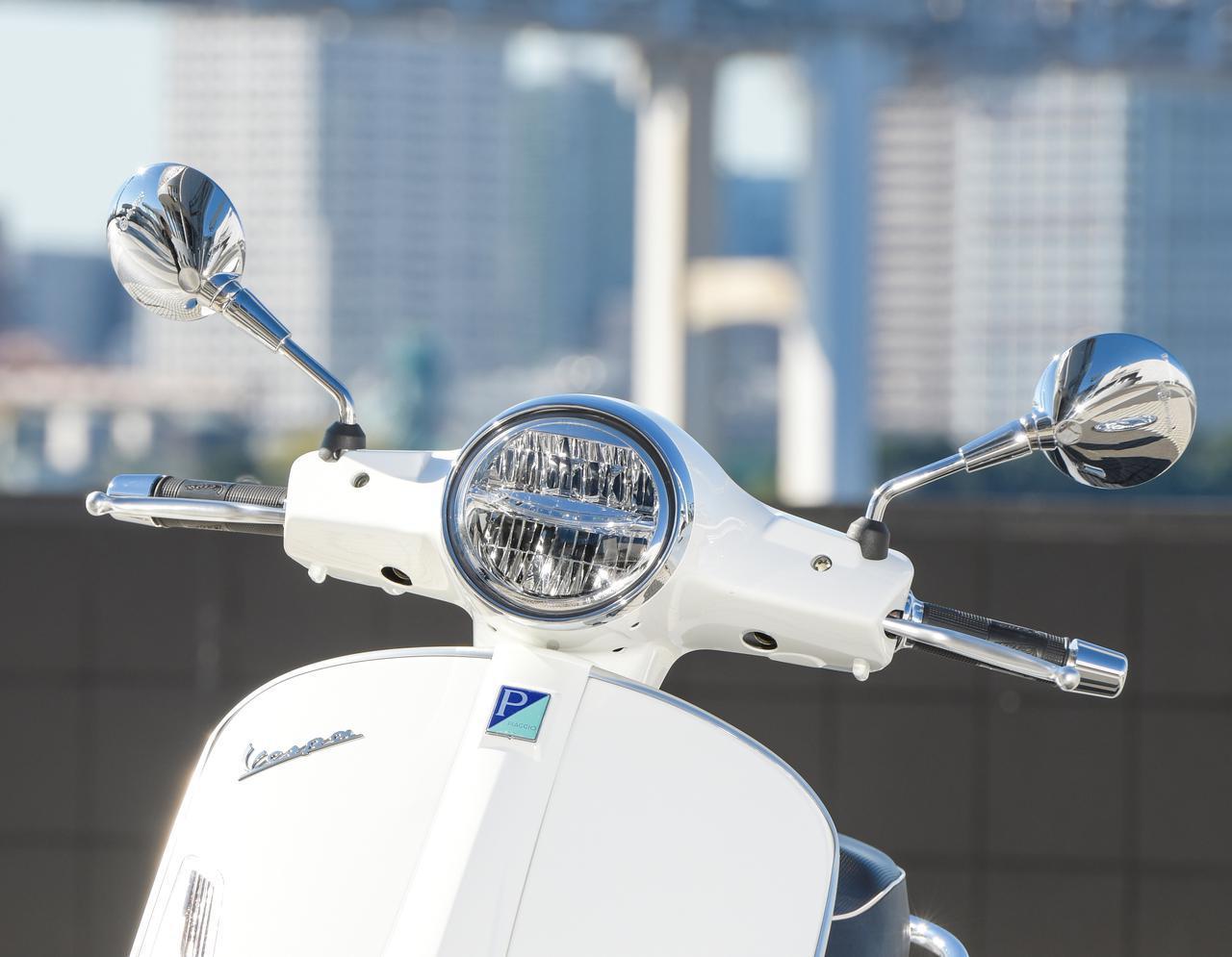 画像: ベスパの伝統的イメージを壊さないクラシカルな丸型ヘッドライトだが、前面をスラントさせるデザインによって現代的にアレンジ。光源にはLEDが採用されていて、視認性などの機能面は最新モデルと変わらないレベルを確保している。