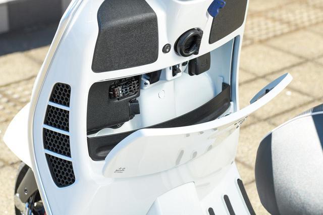 画像: レッグシールド内側に設けられたフロントトランク。容量は小さいが、小物類を収納するにはピッタリの便利な装備。内部にUSB給電ポートが用意されていて、スマートフォンなどの充電もできる。