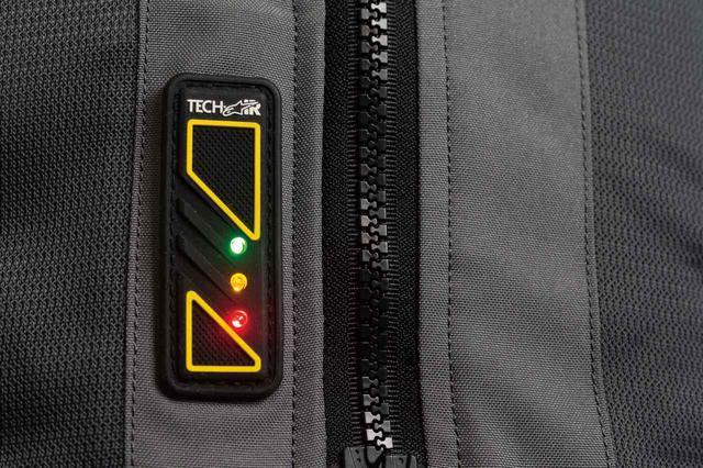 画像: 前合わせジッパー横のLEDディスプレイでエアバッグの状態とバッテリー残量を確認できる。フル充電での駆動時間は約30時間。