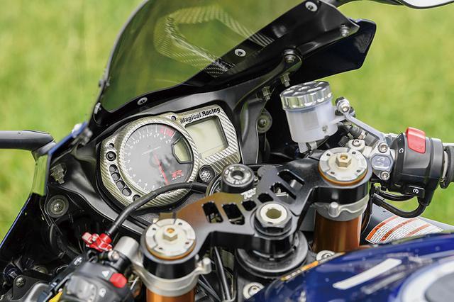 画像: 肉抜き加工も施されたトップブリッジはTG-RUNのスペシャルで、チタンコートスクリーンとシルバーカーボンのメーターカバーはマジカルレーシング製。フロントマスターシリンダーはブレンボラジアル、ワイヤ式のクラッチはレバーをZETAに換装している。
