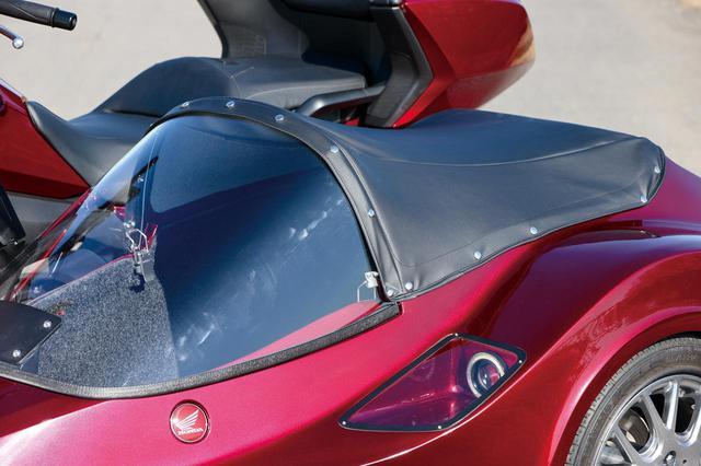 画像: パッセンジャーの肩から下を覆う大型スクリーンのおかげで、走行風はほぼ皆無で非常に快適。保管時はトノカバーを付けておく。