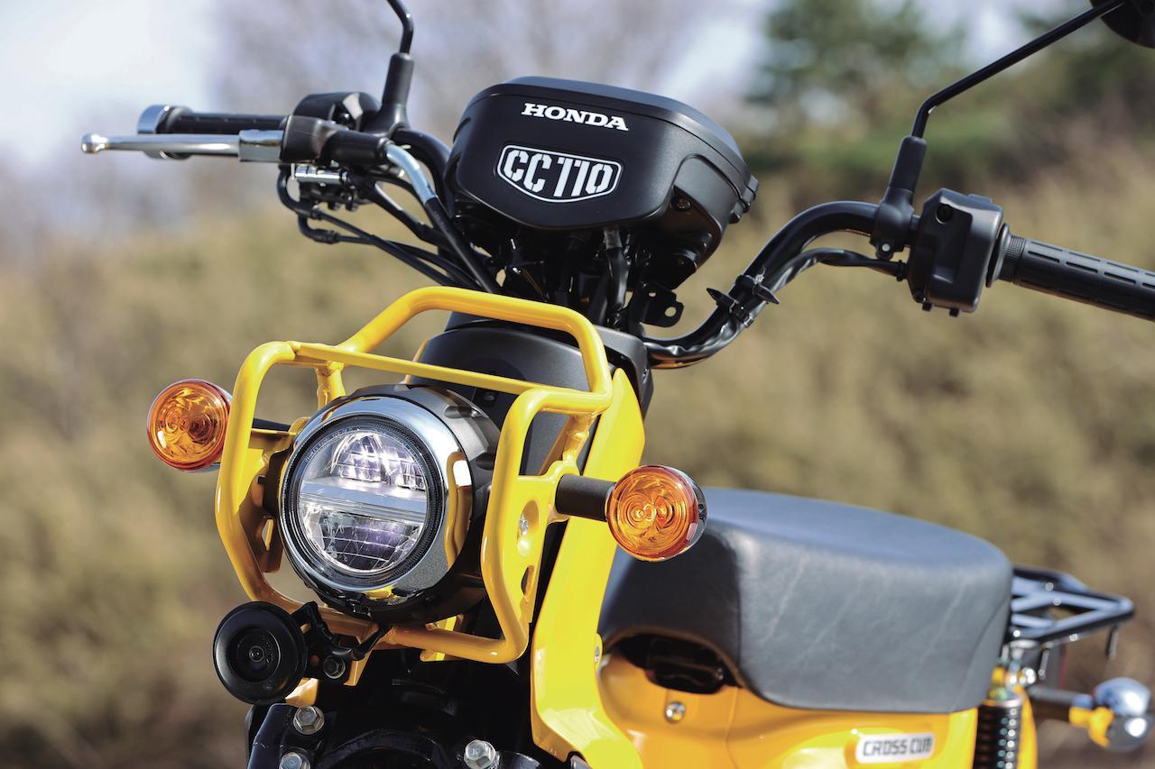 画像: 堅牢なスチールパイプ製のガードと組み合わされるヘッドライトはカブ譲りのLED。ウインカーはオーソドックスな電球式。
