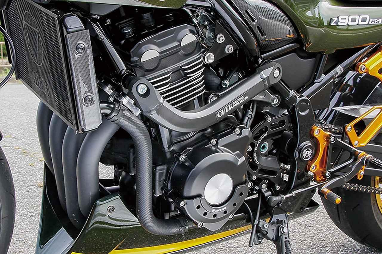 画像: エンジンサイドにオーヴァーレーシング製サブフレームを追加、スプロケットカバーもオーヴァーでインジェクションカバーとラジエーターシュラウドカバーはカーボンに変更。ラジエーターコアにはBEET製コアガードなど、複数メーカーのパーツをバランス良く配置している。