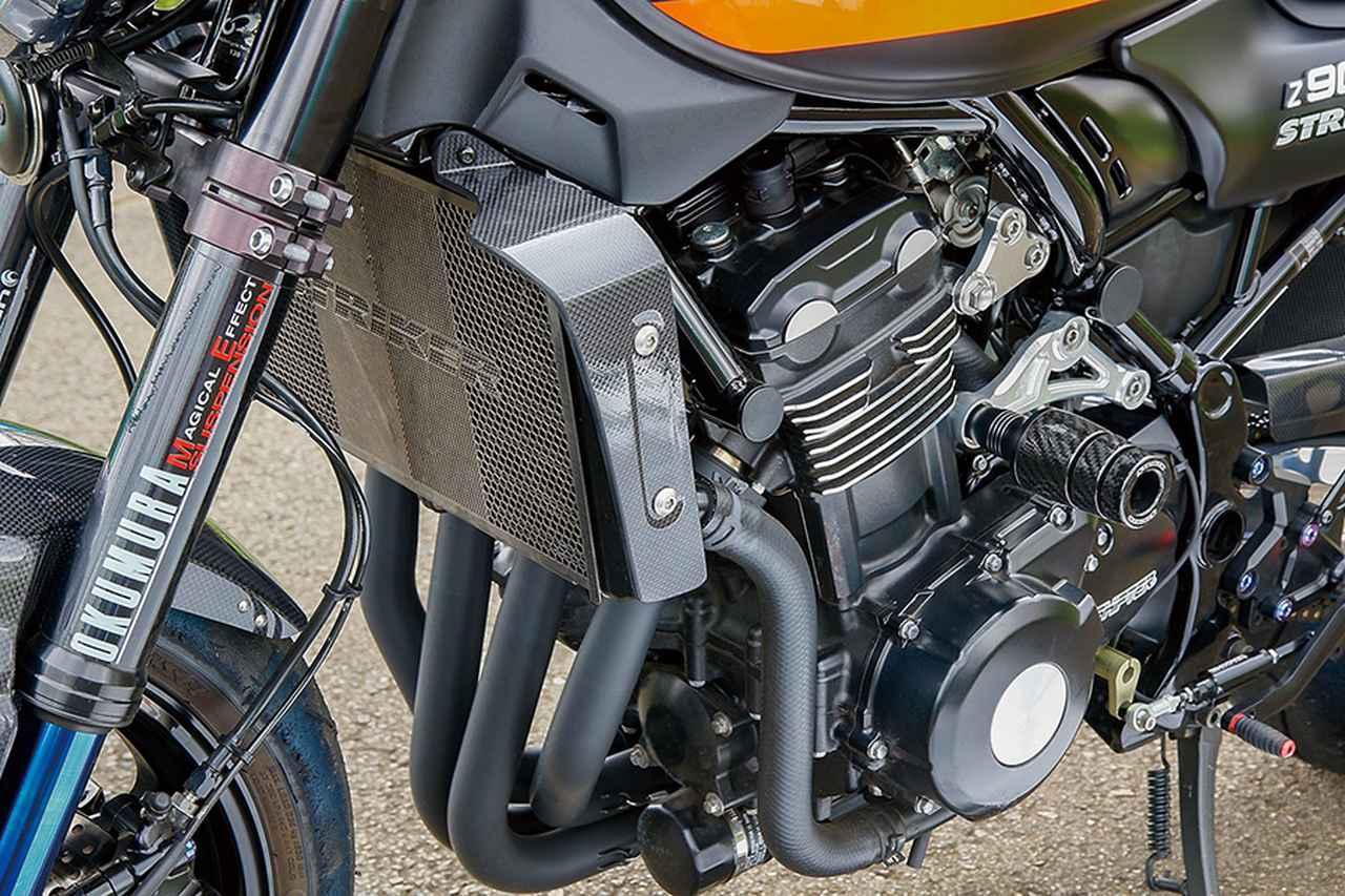 画像: エンジン本体や/FIおよび鋼管トレリスタイプのフレームなどはZ900RSノーマルだが、ラジエーターにはコア前側にラジエーターコアガード、両サイドにSADカーボンラジエターサイドシュラウドを装着する。前後のエンジンハンガーは今回新たにSTRIKERアルミビレットエンジンハンガーに変更。シリンダー側ハンガーの前マウント部にはSTRIKERガードスライダー・カーボンコンポジット仕様も装着した。