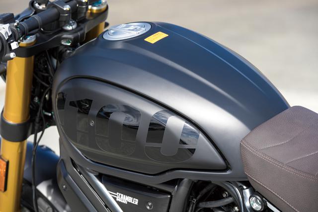 画像: スクランブラーシリーズの個性的スタイルを象徴するパーツであるティアドロップ形状の燃料タンク。クールなイメージのマットブラックにペイントされ、交換可能なサイドパネルには「1100」ロゴが入れられている。容量は15Lを確保。