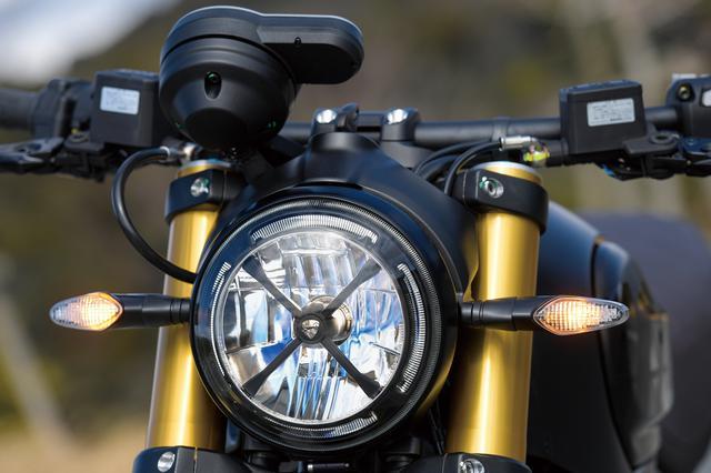 画像: かつてのオフロードモデルが装備していたヘッドライトを保護するテープをモチーフに、LEDヘッドライト前面にブラックメタル製のX形状フレームを装着して、スクランブラーらしさを強くアピールしている。