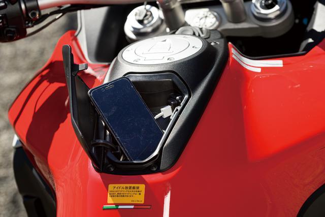 画像: 燃料タンク上、給油口のすぐ後ろには、蓋つきの小物入れスペースが用意されている。内部にはUSBポートも備えていて、スマートフォンを収納して充電をすることができる。