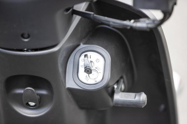 画像: イグニッションスイッチの右側には3輪スクーターの特徴であるパーキングレバーを備える。
