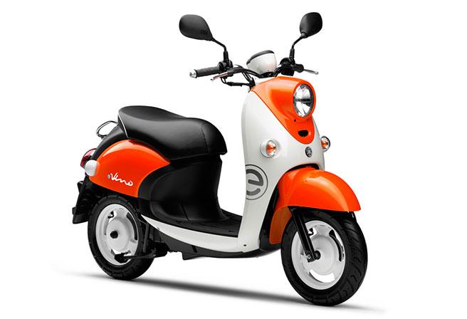 画像: 2015年8月発売の初代E-Vino。カラーリングはビビッドイエローイッシュレッドメタリック1(オレンジ/ホワイト)と、ホワイトメタリック1(ホワイト)の2色を用意。ICE(内燃機関)車のVino同様、カジュアル志向の10~20代前半の女性層に似合う、カラーリング設定です。なお価格は236,520円(税込)でした。 global.yamaha-motor.com