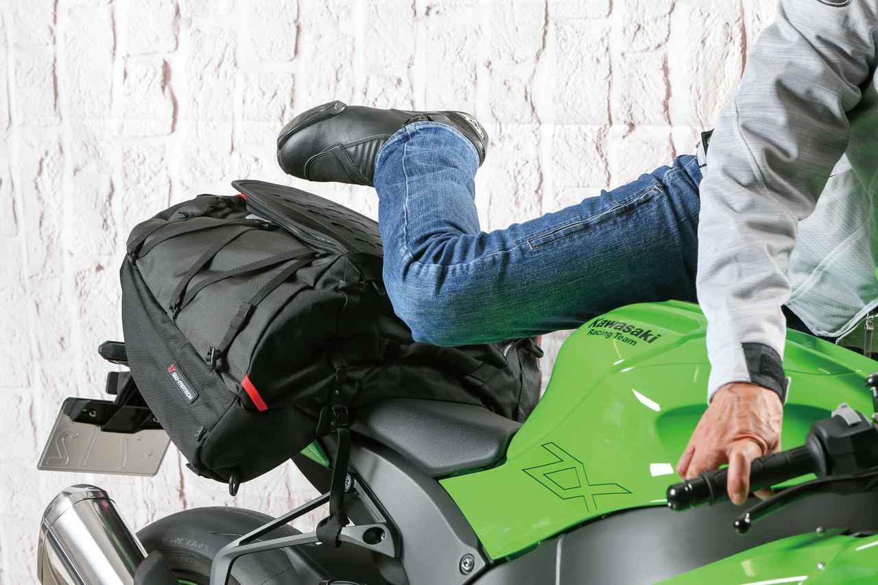 画像: テールバッグ装着時は乗降性が問題になるが、この製品は普通に足を上げて跨がれる。タンデムシート前側にフラップを引っかけることで後ろへのズレも抑止。