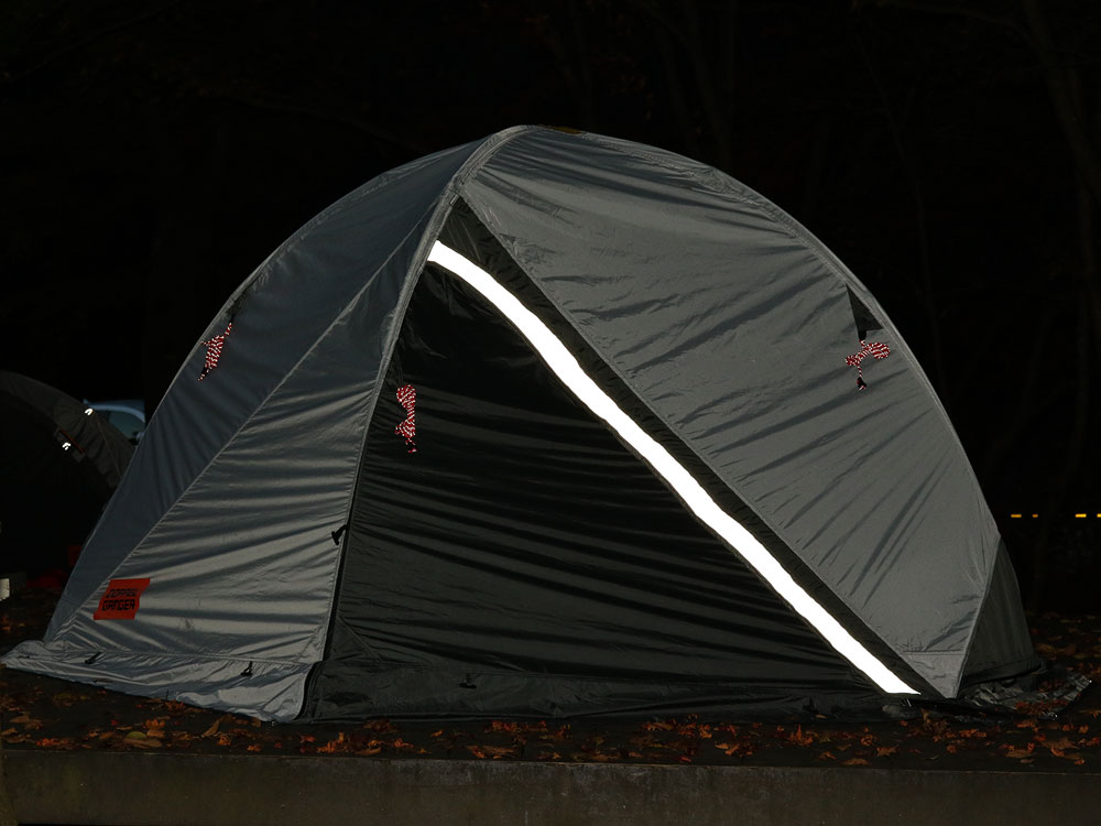 画像: テントの前後入り口に反射板が設けられ、キャンプ場で他車に自身の存在をアピール。事故を未然に防ぐ対策が施されている。