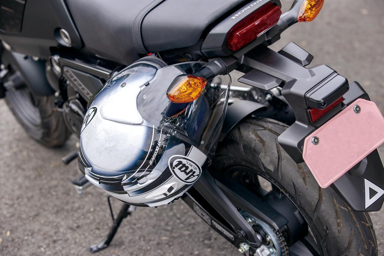 画像: ヘルメットホルダーは、脱着式のシート下フレームに設けられたフックに掛けるタイプとなる。