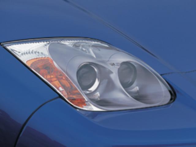画像: 従来のリトラクタブルからプロジェクタータイプディスチャージヘッドライトへ変更 。この他にもリアコンピネーションランプやフロントバンパ ー、リアバンパースカートなどスタイリングを一 新し、空力性能も向上させている。同様に、内装のメーター盤面やパネル類、オーディオやエアコンのスイッチ類にも新色を採用した。 www.motormagazine.co.jp